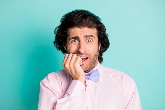 Foto portret van angstige man nagels bijten geïsoleerd op pastel cyaan gekleurde achtergrond
