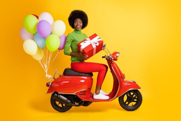Foto portret van brunette afro-amerikaanse vrouw met geschenkdoos op motorfiets met ballonnen in casual rode en groene kleding geïsoleerd op levendige geel gekleurde achtergrond