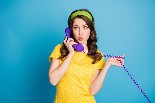 Foto portret van meisje roddelen over paarse bedrade telefoon geïsoleerd op pastel lichtblauw gekleurde achtergrond