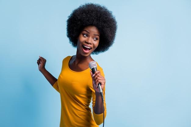 Foto portret van mooi zwart gevild meisje zingen op microfoon met draad op het podium geïsoleerd op levendige blauwe kleur achtergrond