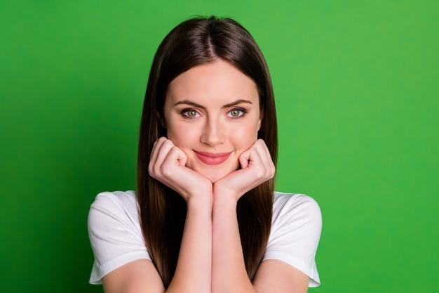 Foto portret van schattig meisje met hoofd gezicht met twee handen geïsoleerd op levendige groen gekleurde achtergrond