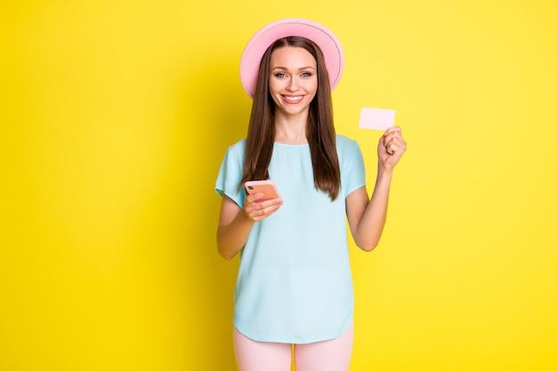 Foto positief meisje volg sociale media aankoop gebruik smartphone betaal creditcard bankkaart draag roze blauw t-shirt zonnehoed broek broek geïsoleerd over heldere glans kleur achtergrond