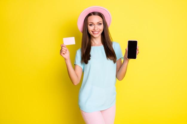 Foto positieve meisje shopper kopen nieuwe moderne technologie smartphone betalen creditcard promo code voucher verkoop draag blauw roze t-shirt broek broek zonnehoed geïsoleerd heldere glans kleur achtergrond