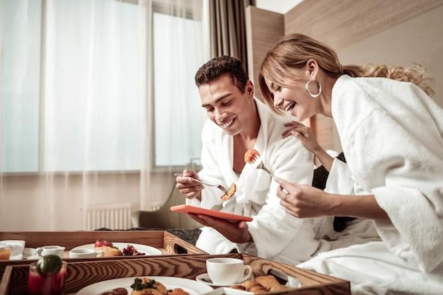Foto's kijken. paar dat heerlijk ontbijt in hotelbed eet en foto's van hun reis bekijkt