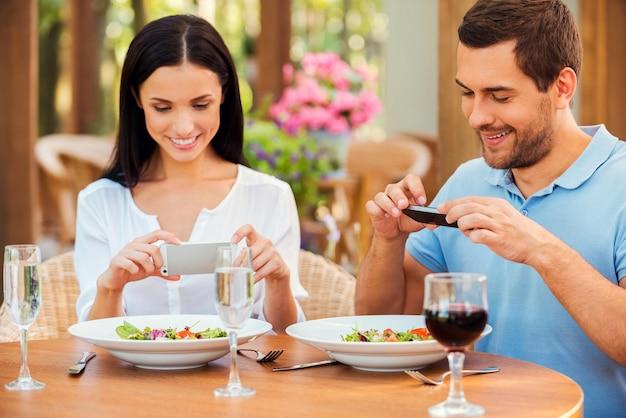 Foto's maken van eten. mooie jonge verliefde koppels die foto's maken van hun eten en glimlachen terwijl ze samen in het openluchtrestaurant ontspannen