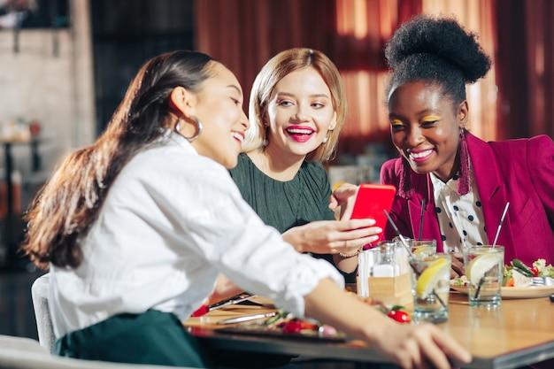 Foto's op telefoon drie beste vrienden die hardop lachen terwijl ze hun foto's op de telefoon bekijken