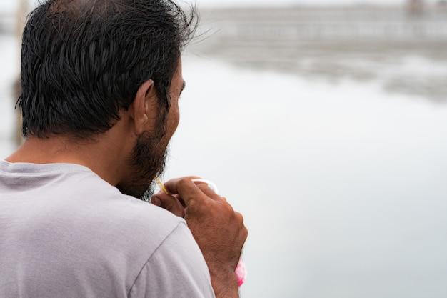 Foto's van achteren, een kortharige man met een baard, die frisdranken drinkt aan zee