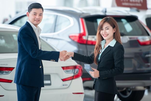 Foto's van aziatische klanten en verkopers kopen hand in hand graag nieuwe auto's die verkoopovereenkomsten sluiten met autodealers bij autodealers.