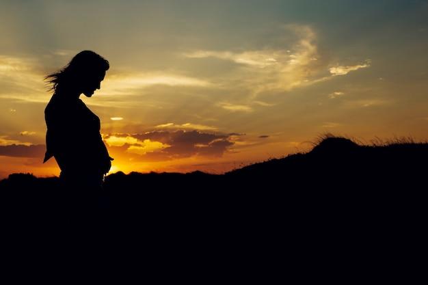 Foto's van de buik van zwangere vrouwen in aard met natuurlijke achtergrond en achtergrondverlichting bij zonsondergang