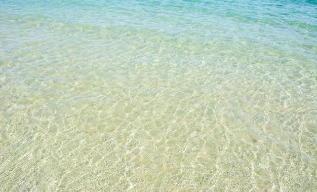 Foto's van helder zeewater kunnen het witte zand zien.