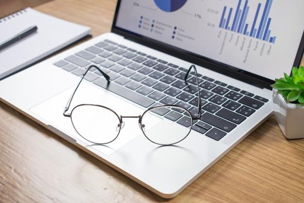 Foto's van het bureau met een laptop en een bril op een houten tafel.