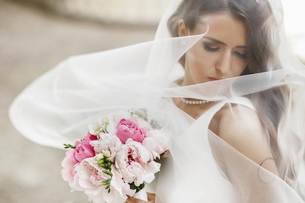 Foto's van het schitterende bruid stellen onder de sluier buiten