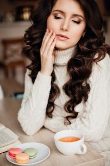 Foto's van mooie brunette met lang haar en perfecte make-up om gebreide jurk te dragen, ogen dicht, raakt de hand van zijn gezicht. op de tafel een kopje thee of koffie en snoep, macaron.