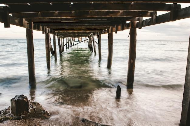 Foto's van onder de houten brug die zich uitstrekte naar de zee