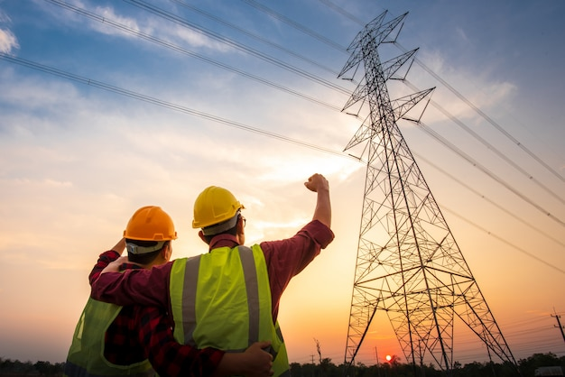 Foto's van twee elektrotechnici die bij de centrale staan om succes te zien en zich te verheugen. met de productie van elektrische stroom