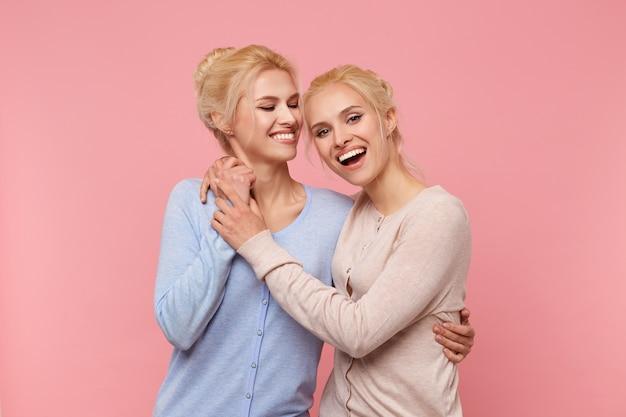 Foto's van twee zussen, knuffelen elkaar en houden elkaars hand vast: blij dat ze elkaar hebben - ze zijn altijd leuk samen! glimlacht breed stads over roze achtergrond.