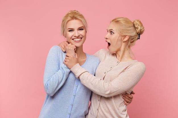 Foto's van tweelingen, elkaar omhelzen en elkaars hand vasthouden, de ene zus verbaast zich over de tweede, die breed lacht en in de camera kijkt, stads op roze achtergrond.