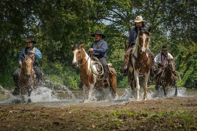Foto's van veel mannen die cowboykleding dragen, op paarden rijden en over de rivier reizen