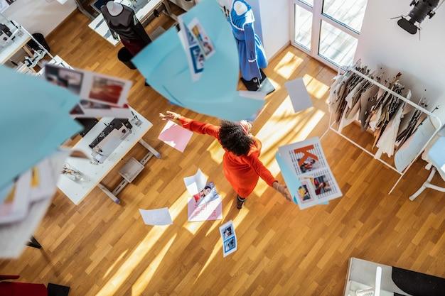 Foto's weggooien. vrolijke jonge ontwerper die zich vrij en gelukkig voelt terwijl hij met stukjes papier in de lucht dwarrelt