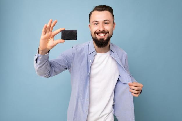 Foto schot van knappe lachende brunette bebaarde jonge man dragen stijlvol blauw shirt en wit t-shirt geïsoleerd over blauwe achtergrond muur met creditcard camera kijken