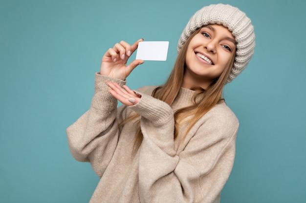 Foto schot van mooie sexy positieve lachende jonge donkerblonde vrouw dragen beige trui en gebreide beige hoed geïsoleerd over blauwe achtergrond houden en tonen creditcard camera kijken