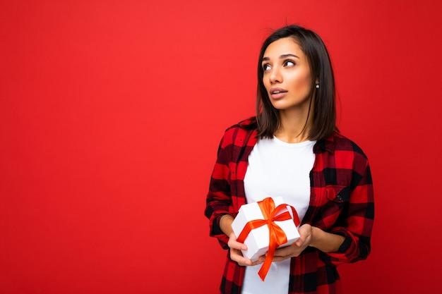 Foto schot van vrij positieve nadenkende jonge brunette vrouw geïsoleerd over rode achtergrond muur