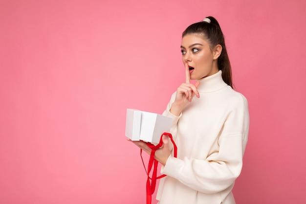 Foto shot van aantrekkelijke geschokt jonge brunette vrouw geïsoleerd over roze achtergrond muur dragen