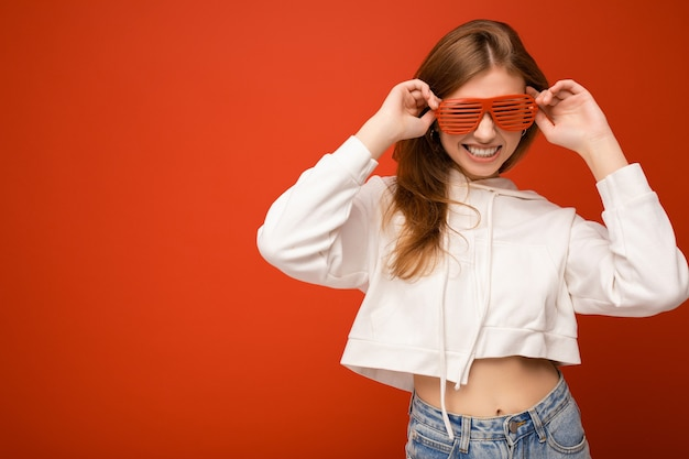 Foto shot van mooie positieve jonge blonde vrouw, gekleed in casual kleding en een stijlvolle optische bril