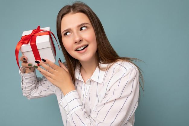 Foto shot van vrij positief verrast jonge donkerblonde vrouw geïsoleerd over kleurrijke achtergrond muur trendy outfit dragen kijken geschenkdoos houden en kijken naar huidige doos met rood lint.
