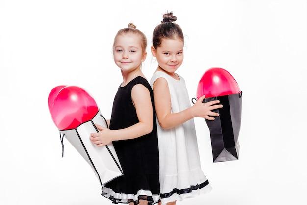 Foto van 2 kleine meisjes met elegante jurken met grote tassen met hartvormige ballonnen erin