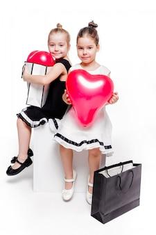 Foto van 2 kleine meisjes met elegante jurken zitten met grote tassen met hartvormige ballonnen erin
