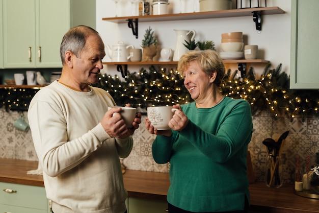 Foto van 60s bejaarde echtpaar genieten van het leven in de keuken met mokken koffie. valentijnsdag van oude verliefde stelletjes. stop discriminatie op grond van leeftijdsdiscriminatie. hoge kwaliteit foto