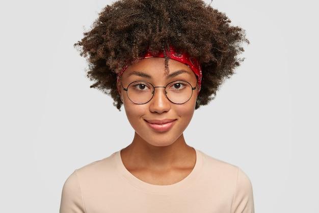 Foto van aangenaam uitziende vrolijke donkere vrouw in ronde brillen