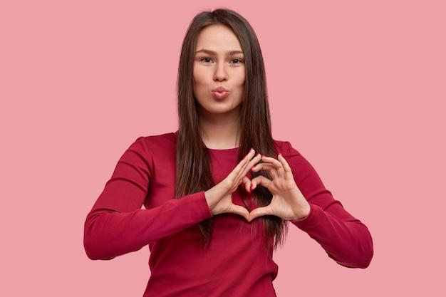 Foto van aangenaam uitziende vrouw maakt lippen rond, toont hartgebaar met vingers, flirt met vriend op afstand, heeft een aantrekkelijk uiterlijk