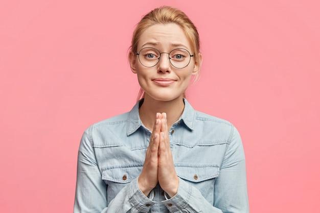 Foto van aantrekkelijk jong vrouwelijk model met smekende uitdrukking, vraagt om haar te helpen in moeilijke situatie, heeft een hulpeloze blik, poseert tegen roze