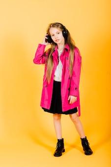 Foto van aantrekkelijk meisje met behulp van draadloze hoofdtelefoons geïsoleerd op gele achtergrond, studio