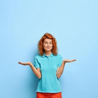 Foto van aantrekkelijk roodharige duizendjarige meisje heft handpalmen op, voelt twijfel, kan niet kiezen tussen twee items, draagt een casual blauw t-shirt, heeft kuiltjes in het gezicht, is onverschillig, voelt aarzeling.