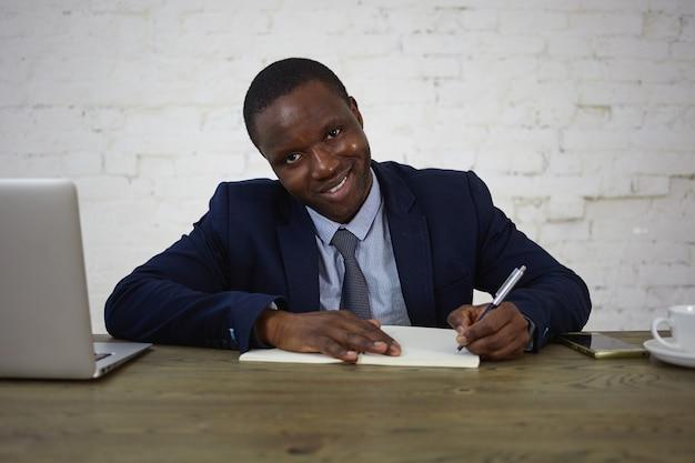 Foto van aantrekkelijke afrikaanse advocaat die pak draagt dat bij zijn bureau werkt, aantekeningen maakt in dagboek, kijkt en glimlacht. gelukkige zakenman die zijn ideeën en plannen in voorbeeldenboek opschrijft