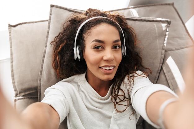 Foto van aantrekkelijke afrikaanse amerikaanse vrouw die hoofdtelefoons draagt die selfie op mobiele telefoon nemen, terwijl liggend op bank in licht appartement