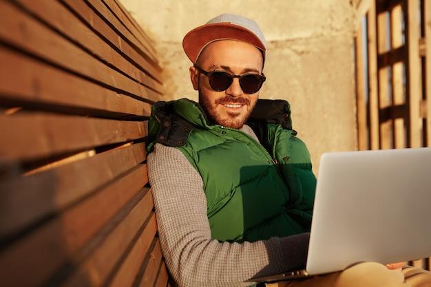 Foto van aantrekkelijke bebaarde jonge europese man in zwarte tinten typen op laptop glimlachen op camera