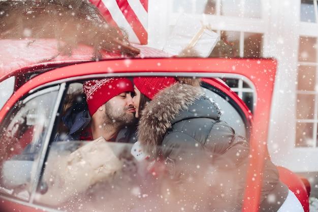 Foto van aantrekkelijke blanke vrouw in warme kleren draagt dozen met kerstcadeaus in een auto naar haar vriendje en kust hem
