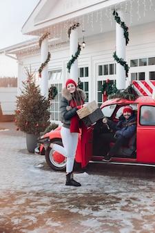 Foto van aantrekkelijke blanke vrouw in warme kleren draagt dozen met kerstcadeaus in een auto naar haar vriendje