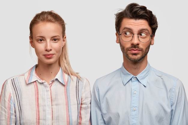 Foto van aantrekkelijke blonde vrouw met paardenstaart, nieuwsgierige ongeschoren man staat schouder aan schouder tegen witte muur, heeft vriendschappelijke relaties. twee collega's komen samen voor het maken van een project