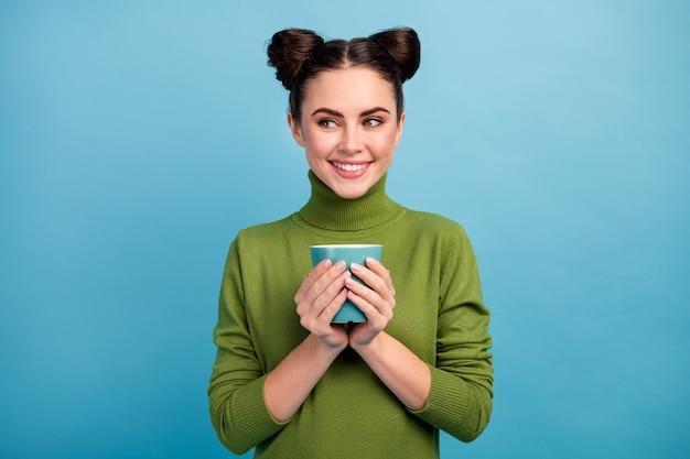 Foto van aantrekkelijke charmante tiener dame houden warme drank kopje thee koffie genieten weekend ochtend kijken kant lege ruimte dragen warme groene coltrui pullover geïsoleerde blauwe kleur muur