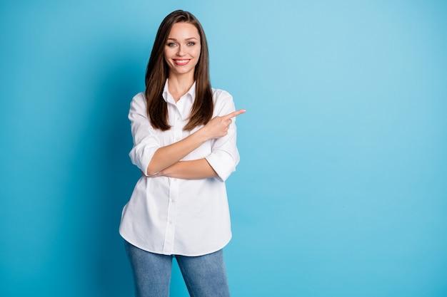 Foto van aantrekkelijke dame directe vinger kant lege ruimte draag wit overhemd jeans geïsoleerde blauwe kleur achtergrond