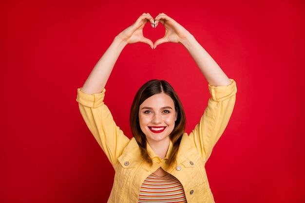 Foto van aantrekkelijke dame goed humeur houdt armen bij elkaar boven het hoofd waardoor vingers hartfiguur uiten hartgevoelens dragen casual gele blazer jas geïsoleerd levendige rode kleur achtergrond
