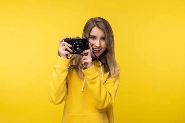 Foto van aantrekkelijke dame houdt camera met glimlach vast en wil een foto maken. draagt casual gele hoody, geïsoleerde gele kleur achtergrond.