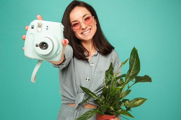 Foto van aantrekkelijke dame houdt camera, plant en glimlacht. draagt grijs shirt, geïsoleerde turquoise kleur achtergrond.