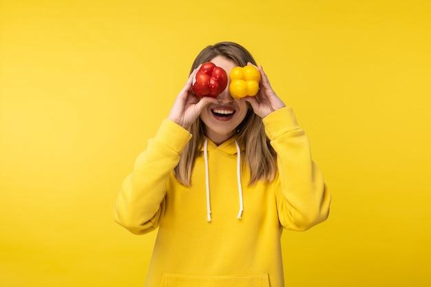 Foto van aantrekkelijke dame houdt papieren en ogen bedekt met een glimlach. draagt casual gele hoody, geïsoleerde gele kleur achtergrond.