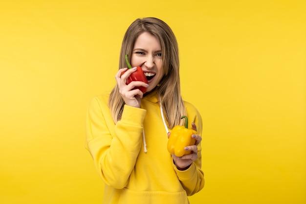 Foto van aantrekkelijke dame houdt papieren vast en bijt erin met plezier. draagt casual gele hoody, geïsoleerde gele kleur achtergrond.